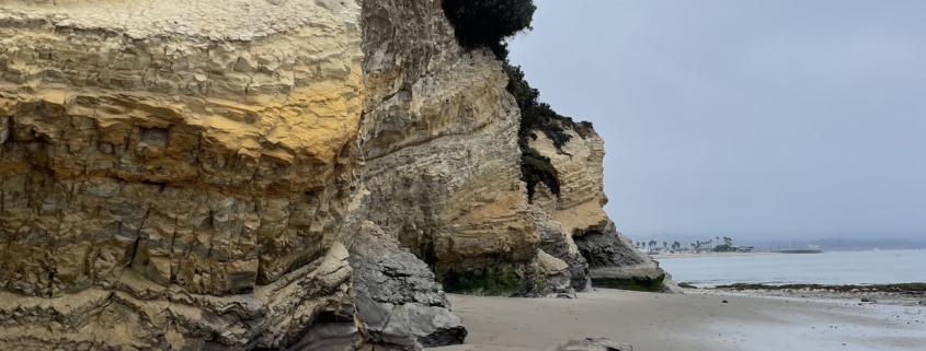 long, sandy beach with sandstone bluffs on the left side