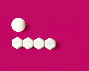 magenta background with one round white tablet and four hexagonal white tablets beneath